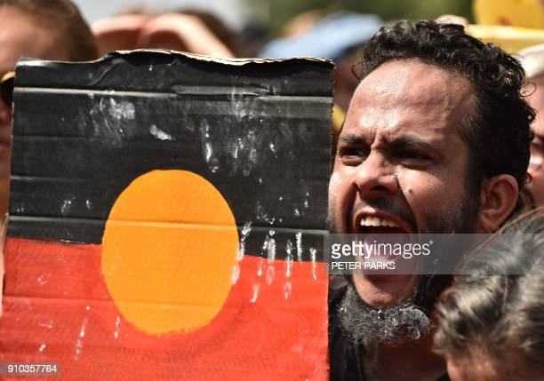A protester holds up a design with the Aboriginal flag during an 'Invasion Day' rally on Australia Day in Melbourne on January 26 2018 Thousands of...