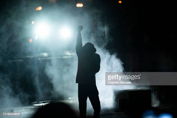 A protester holds up a fist in a cloud of tear gas outside the Third Police Precinct building on May 28 2020 in Minneapolis Minnesota Police and...