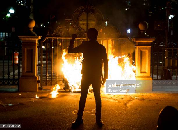 Protester holds up a fist in front of the burning gate of the Boston Public Garden as protestors try to barricade the police out as they get pushed...