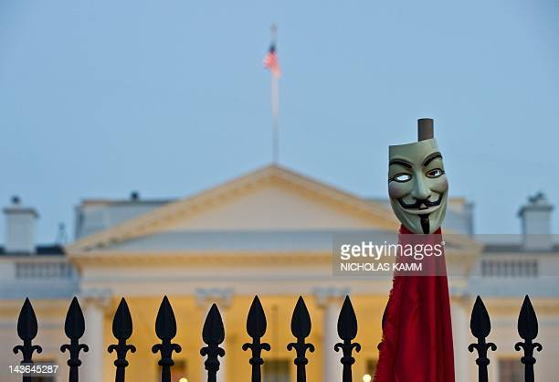 Protester holds up a Guy Fawkes mask as members of Occupy DC and union activists protest in front of the White House during a May Day demonstration...