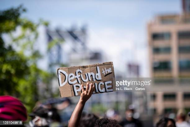 """Protester holds up a homemade sign that says, """"Defund the Police"""" with the Manhattan Bridge behind them as they perform a peaceful protest walk..."""