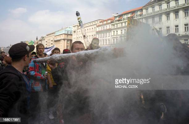 A protester holds up a imitation of a big joint as people take part in a demonstration for the legalization of marijuana in front of the National...