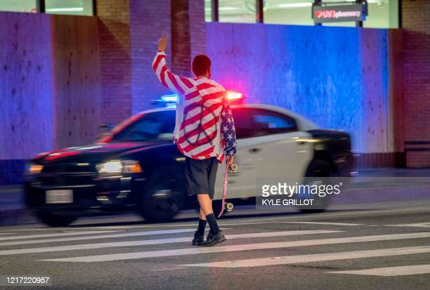 Protester holds up a peace sign as police drive down Hollywood Boulevard after curfew during a demonstration over the death of George Floyd while in...