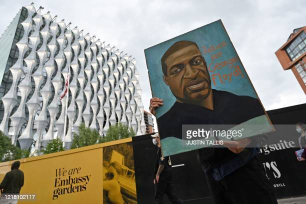 Protester holds up a picture of George Floyd at a demonstration outside the US Embassy in London on June 7 organised to show solidarity with the...