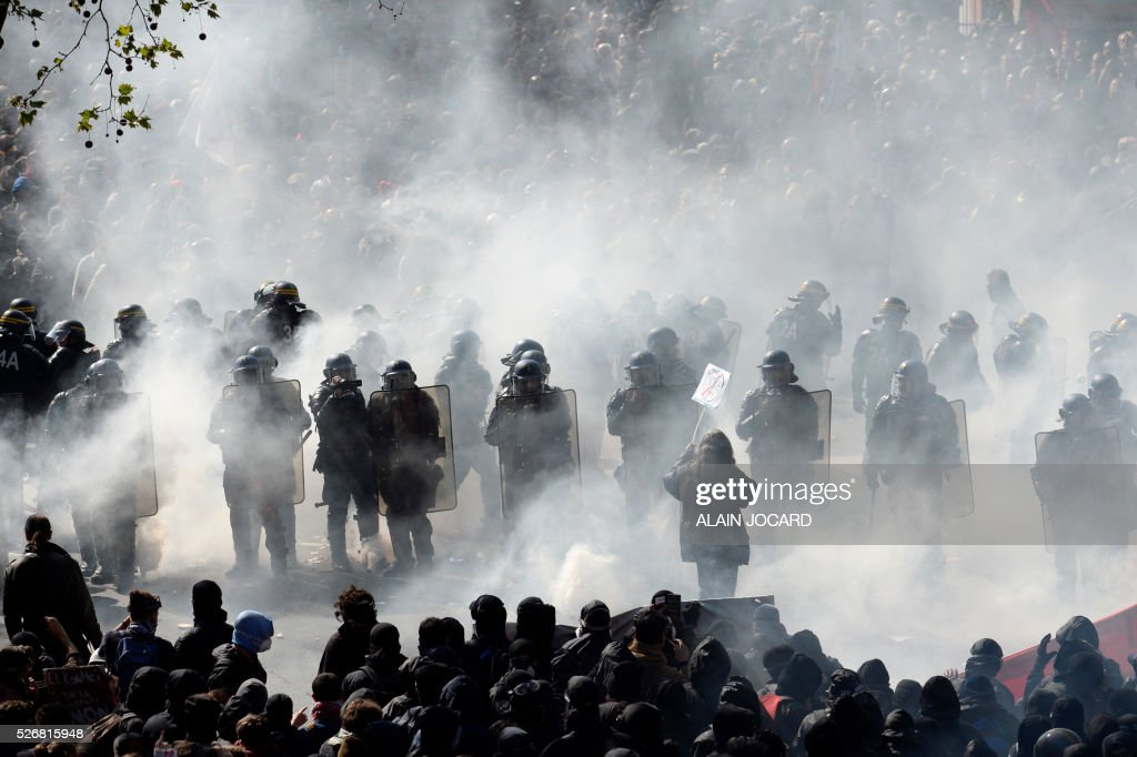 TOPSHOT - A protester holds up a placard as French anti riot police are surrounded by smoke during a clash during the traditional May Day demonstration in Paris on May 1, 2016. / AFP / ALAIN