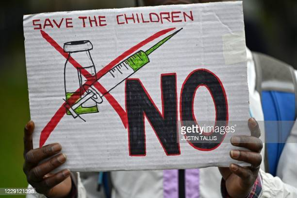 Protester holds up a placard at a demonstration against vaccinations and government restrictions designed to fight the spread of the novel...