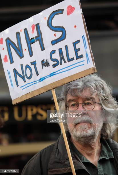 A protester holds up a placard during a march through central London in support of the NHS on March 4 2017 in London England Thousands march from...