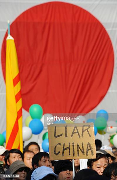A protester holds up a placard saying 'Liar China' during an antiChina protest rally in central Tokyo on November 6 2010 Japanese national flags...