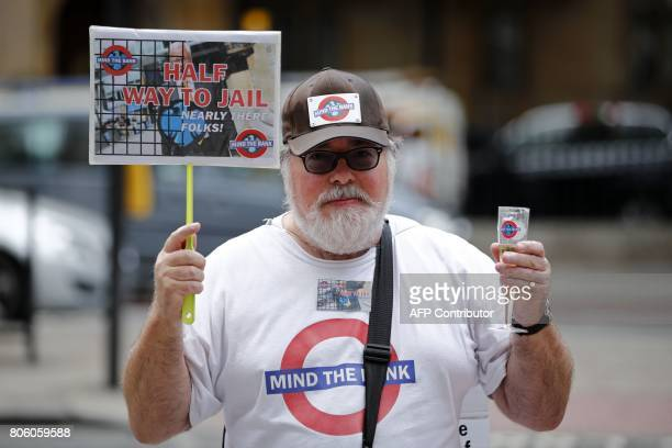 A protester holds up a placard taunting Barclays outside Westminster Magistrates Court in central London on July 3 2017 Barclays bank and four former...