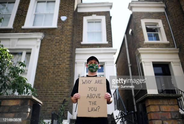 A protester holds up a placard which reads 'Why are you above the law' outside the home of Dominic Cummings Chief Advisor to Prime Minister Boris...