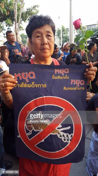A protester holds up a poster saying 'Don't delay an election stop clinging to power stop dictatorship' during a rally near Democracy Monument in...