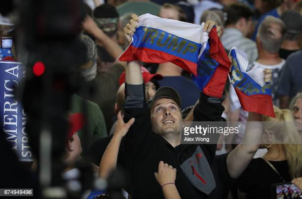 A protester holds up a Russia/Trump flag as US President Donald Trump speaks to supporters during a 'Make America Great Again Rally' at the...