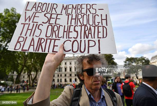 A protester holds up a sign accusing Labour members of a 'Blairite Coup' during Momentum's 'Keep Corbyn' rally outside the Houses of Parliament on...