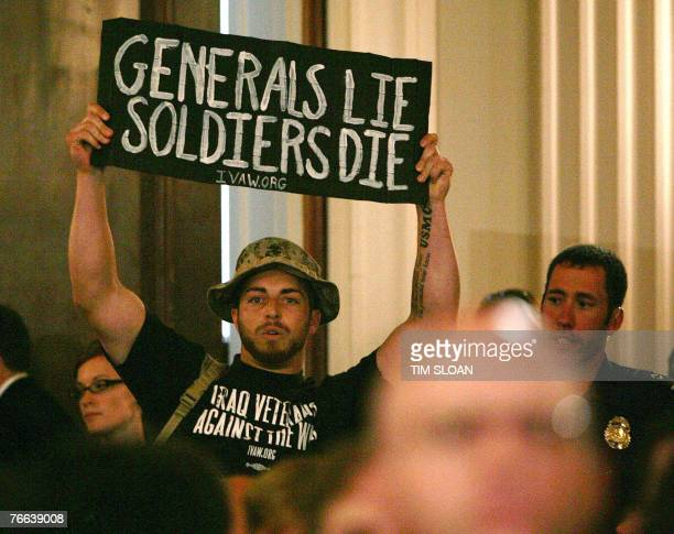 A protester holds up a sign before being escorted out by Capitol Hill Police during testimony from the US Commander in Iraq General David Petraeus...