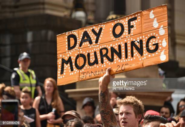 """Protester holds up a sign during an """"Invasion Day"""" rally on Australia Day in Melbourne on January 26, 2018. Thousands of supporters joined rallies..."""