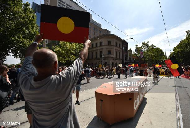 A protester holds up a sign in front of a mock coffin during an 'Invasion Day' rally on Australia Day in Melbourne on January 26 2018 Thousands of...