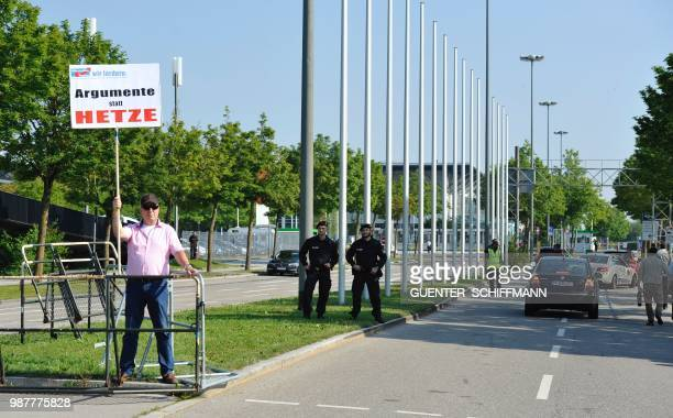 A protester holds up a sign reading 'Arguments instead of agitation' in front of the entrance of the venur where a twoday party congress of Germany's...