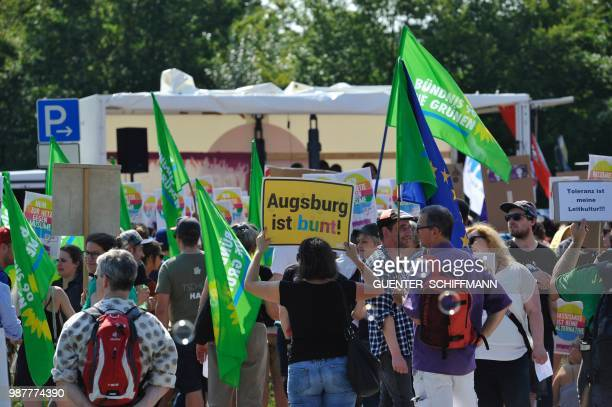 A protester holds up a sign reading 'Augsburg is colourful' at the start of a twoday party congress of Germany's farright and antiimmigration party...