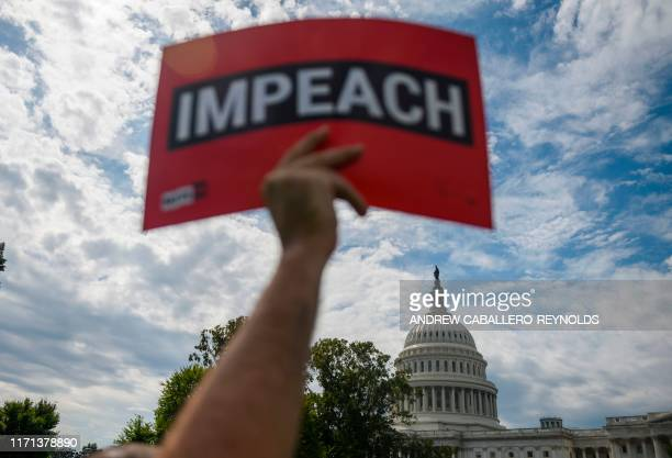 "Protester holds up a sign reading ""impeach"" outside the US Capitol building during the ""People's Rally for Impeachment"" on Capitol Hill in..."