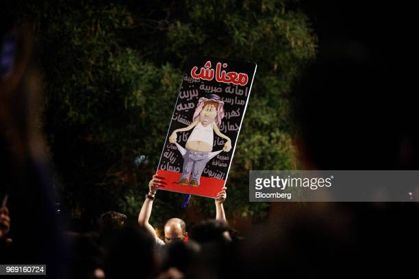 A protester holds up a sign reading 'We Have Nothing' during a demonstration against a draft income tax law near the prime minister's office in Amman...