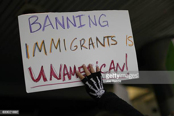 A protester holds up a sign that reads 'Banning Immigrants is UnAmerican' as she stands with others at the Miami International Airport against the...