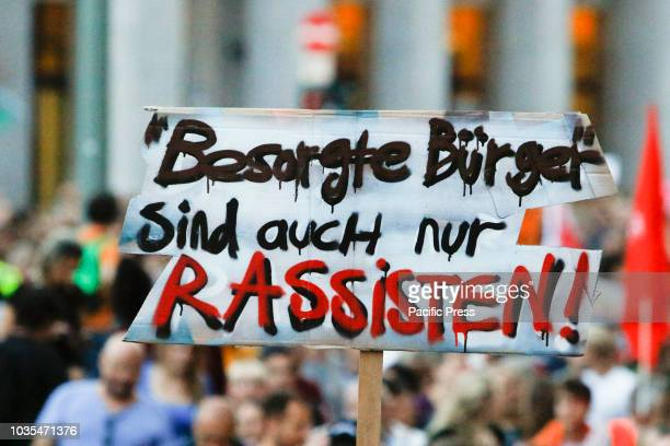 A protester holds up a sign that reads 'Concerned citizens are only racists' Around 6300 protesters marched through Frankfurt in support of the...