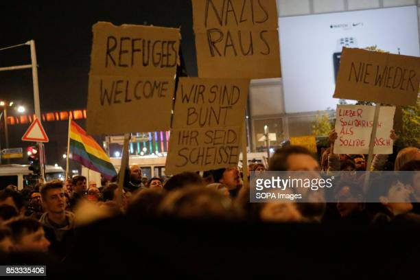 Protester holds up a sign that reads 'Refugees Welcome' 'Nazis out' 'We are colourful You are shit' and 'Never again' Hundreds of protesters gathered...