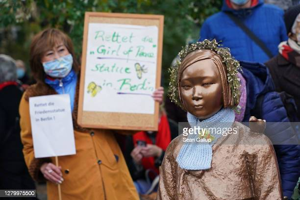 """Protester holds up a sign that reads: """"Save the 'girl of peace' statue in Berlin"""" next to a memorial to World War II Korean """"comfort women"""" at a..."""