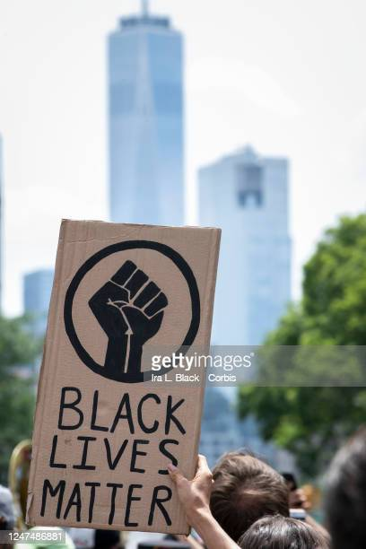 A protester holds up a sign with a black power fist and the words Black Lives Matter as they walk down 6th Avenue in Manhattan with the One World...