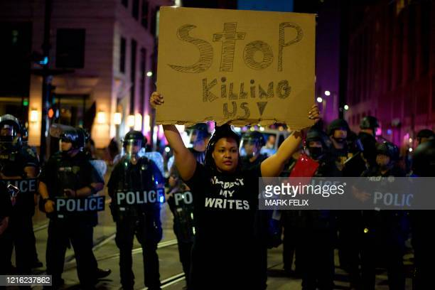A protester holds up a sign with a row of police officers behind during a Justice 4 George Floyd demonstration over the death of George Floyd a black...