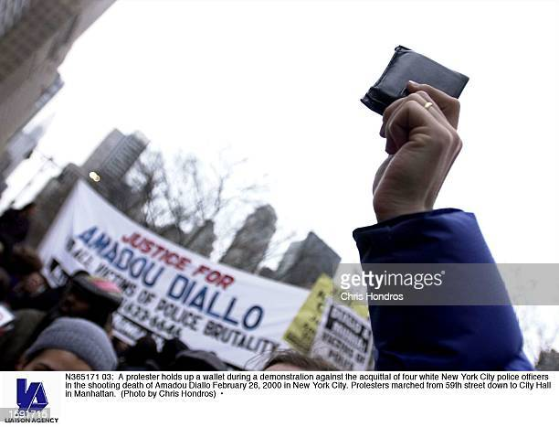 A protester holds up a wallet during a demonstration against the acquittal of four white New York City police officers in the shooting death of...