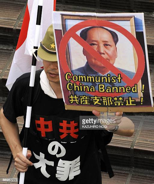 A protester holds up an anticommunist China placard during a demonstration in Tokyo on July 12 2009 Some 50 Uighur expatriates and hundreds of their...