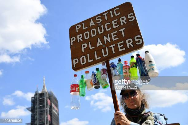 Protester holds up an anti-plastics placard as activists from the climate protest group Extinction Rebellion gather in Parliament Square on September...