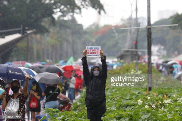 Protester holds up an anti-terror bill placard as others march at a university campus in Manila on June 12, 2020. - Lawmkers earlier this month...