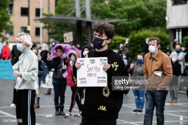 Protester holds up aplacard with the names of racist violence during a socially distanced demonstration takes place at Custom House Square in support...
