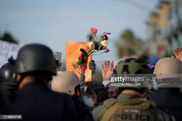 TOPSHOT A protester holds up flowers as she confronts a row of police officers during a demonstration over the death of George Floyd while in...