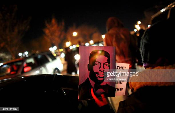 A protester holds up Garner's photo while walking on the West Side Highway December 3 2014 in New York Protests began after a Grand Jury decided to...