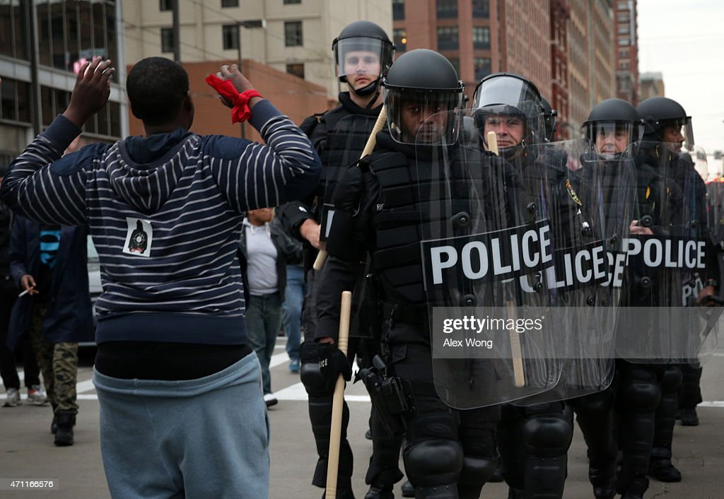 A protester holds up his hands as police in riot gear pass through during a march in honor of Freddie Gray on April 25, 2015 in Baltimore, Maryland. Gray, 25, was arrested for possessing a switch blade knife outside the Gilmor Homes housing project on Baltimore's west side on April 12. According to his attorney, Gray died a week later in the hospital from a severe spinal cord injury he received while in police custody.