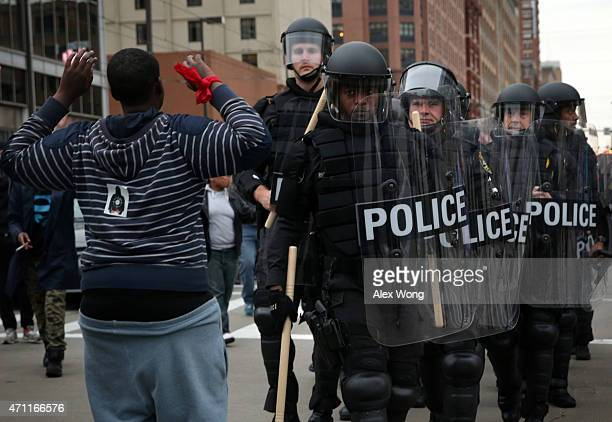 A protester holds up his hands as police in riot gear pass through during a march in honor of Freddie Gray on April 25 2015 in Baltimore Maryland...