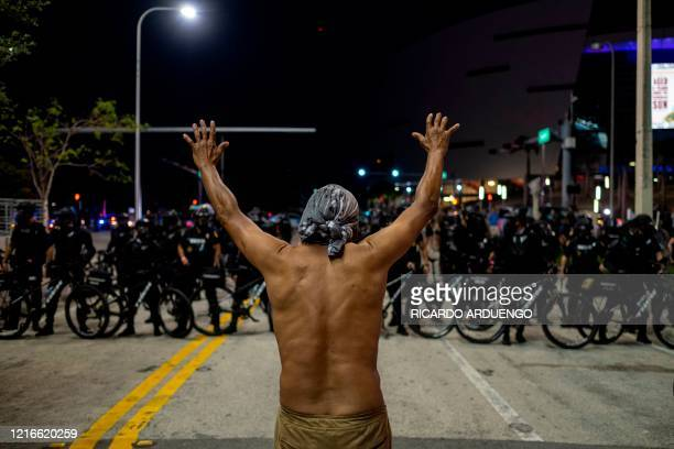 A protester holds up his hands in front of a row of police officers during a rally in response to the recent death of George Floyd an unarmed black...