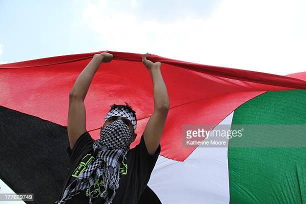 CONTENT] A protester holds up part of a huge Palestine flag at Grant Park during the NATO summit