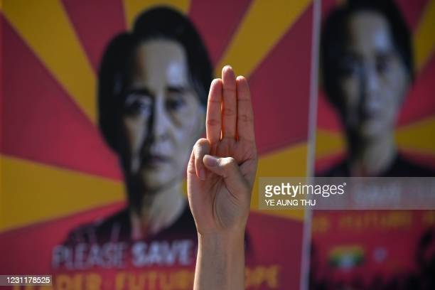 Protester holds up the three finger salute during a demonstration against the military coup outside the US embassy in Yangon on February 15, 2021.