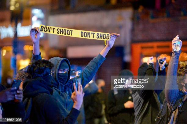 A protester holds up yellow barricade tape reading don't shoot during clashes with police after a demonstration over the death of George Floyd an...