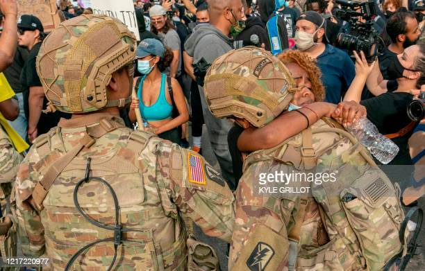 TOPSHOT A protester hugs a member of the National Guard during a demonstration over the death of George Floyd while in Minneapolis Police custody in...