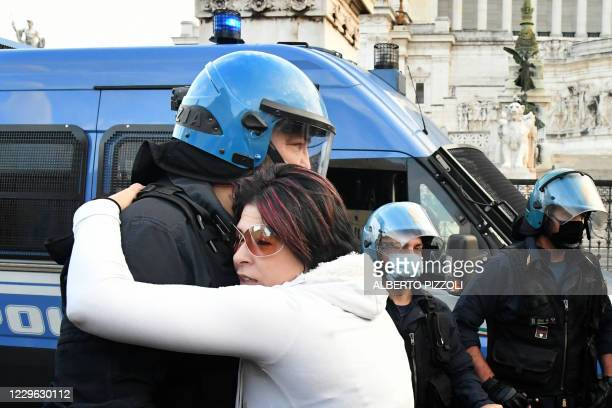Protester hugs a police officer in provocation on November 15 in Rome, during a demonstration of anti-mask supporters and against government...