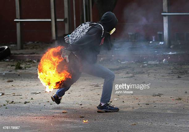 A protester hurls a burning tire at national guard troops during an antigovernment demonstration on March 2 2014 in Caracas Venezuela Venezuela has...
