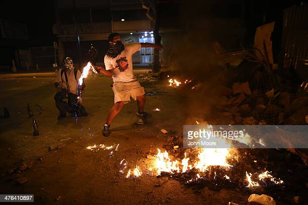A protester hurls a molotov cocktail at national guard troops during an antigovernment demonstration on March 2 2014 in Caracas Venezuela Venezuela...