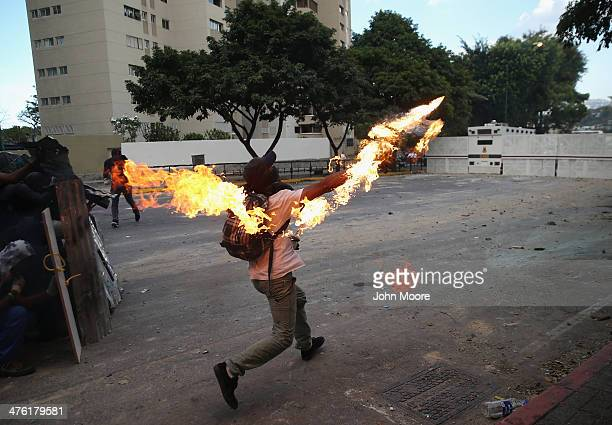 A protester hurls a molotov cocktail at national guard troops in one of the largest antigovernment demonstrations yet on March 2 2014 in Caracas...