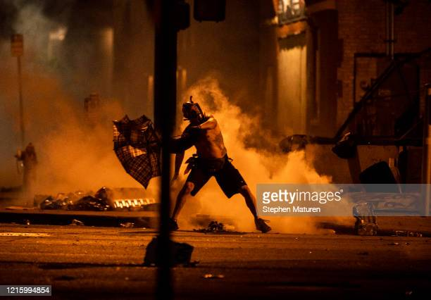 A protester hurls a tear gas canister back at police outside the Third Police Precinct building on May 28 2020 in Minneapolis Minnesota Police and...