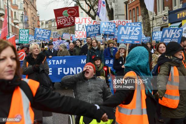 A protester in a wheelchair seen shouting slogans during the demonstration Thousand of people marched in London in a protest called 'NHS in crisis...